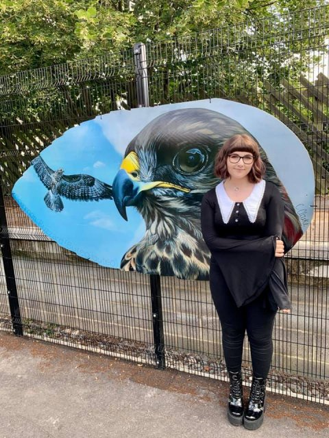 An image of our outdoor art gallery competition winner, Cerys Clarke, with her design, 'The Common Buzzard.'