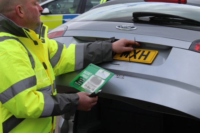 Ian curtis from the nwldc licensing inspection team suspends the license of one taxi driver and removes his plate.