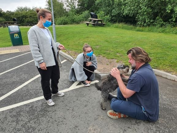 Miniature Schnauzer dog Trouser is reunited with her owner Dan Downes. Image shows a man sitting on the floor cuddling a small grey dog with two Animal Care officers standing next to him.