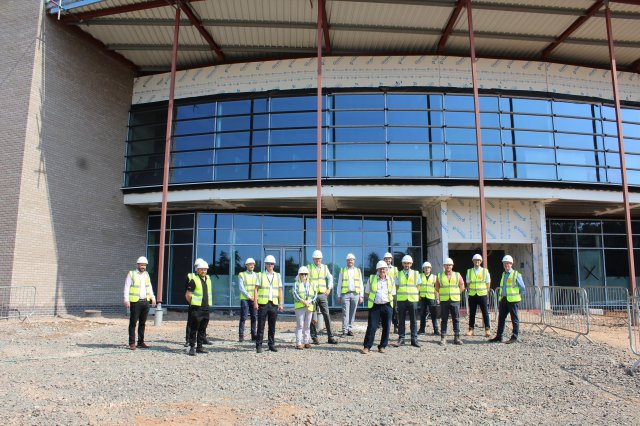 Image showing people in hard hats and hi vis jackets standing outside of the Whitwick and Coalville Leisure Centre - one year into the build