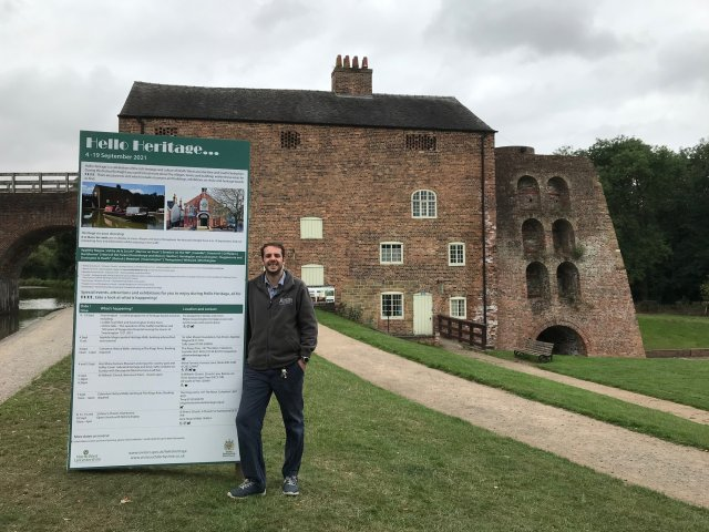 A photo of Tom Phillips, Site Manager at Moira Furnace Museum and Country Park with Hello Heritage board.