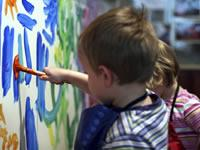 A young child painting colourfully on a wall